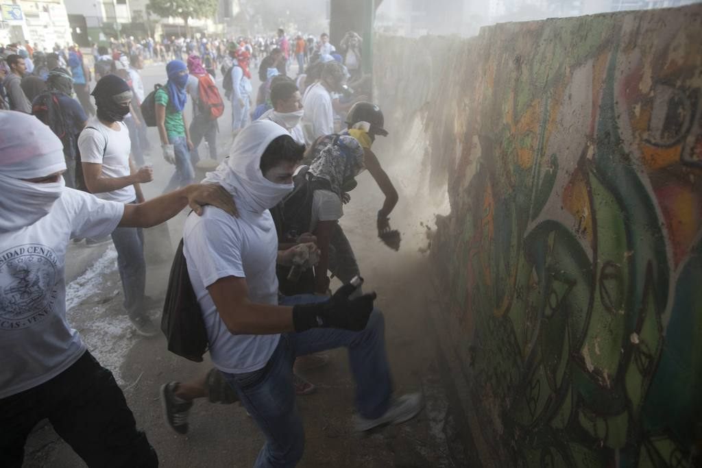 FILE - In this March 4, 2014 file photo, demonstrators destroy a wall in order to have more rocks to throw at the Bolivarian National Guard during ant...