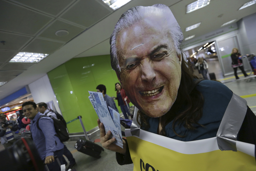 An activist protests dressed with a mask of Brazil's President Michel Temer, while he holds fake 100 Brazilian Real notes, at the arrivals area of the...