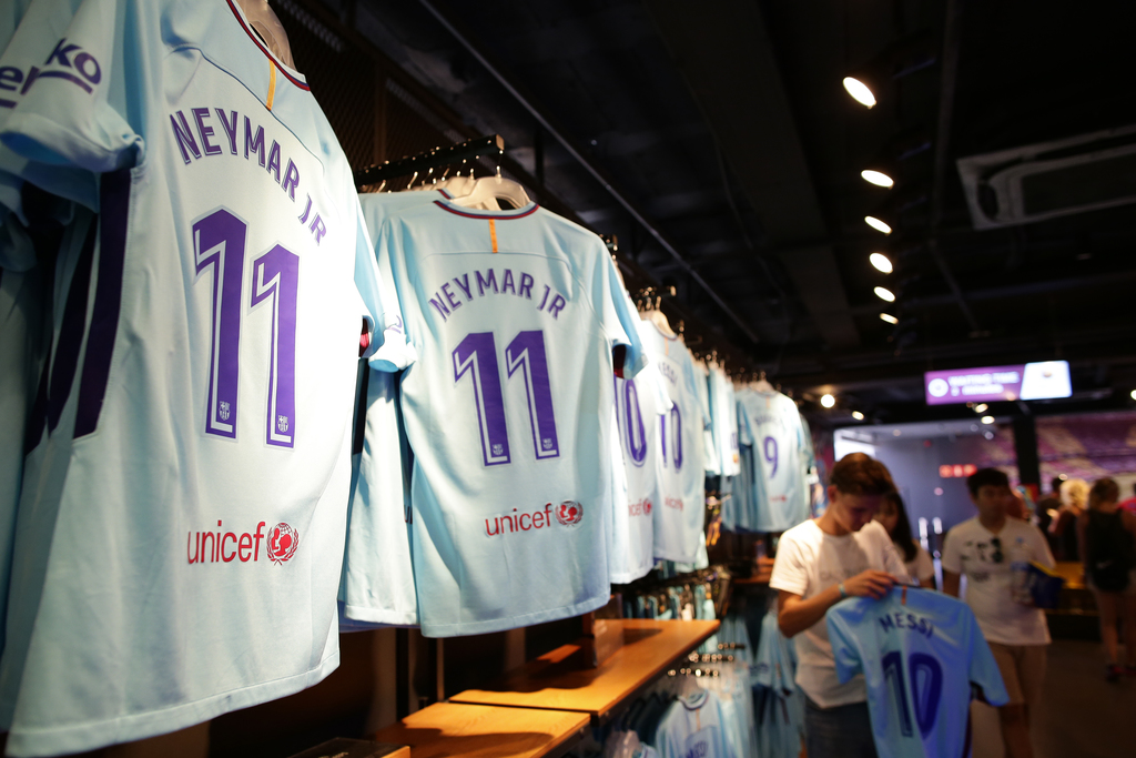 People stand next to t-shirts with the name of FC Barcelona's Neymar in a store of the Camp Nou stadium in Barcelona, Spain, Wednesday, Aug. 2, 2017. ...