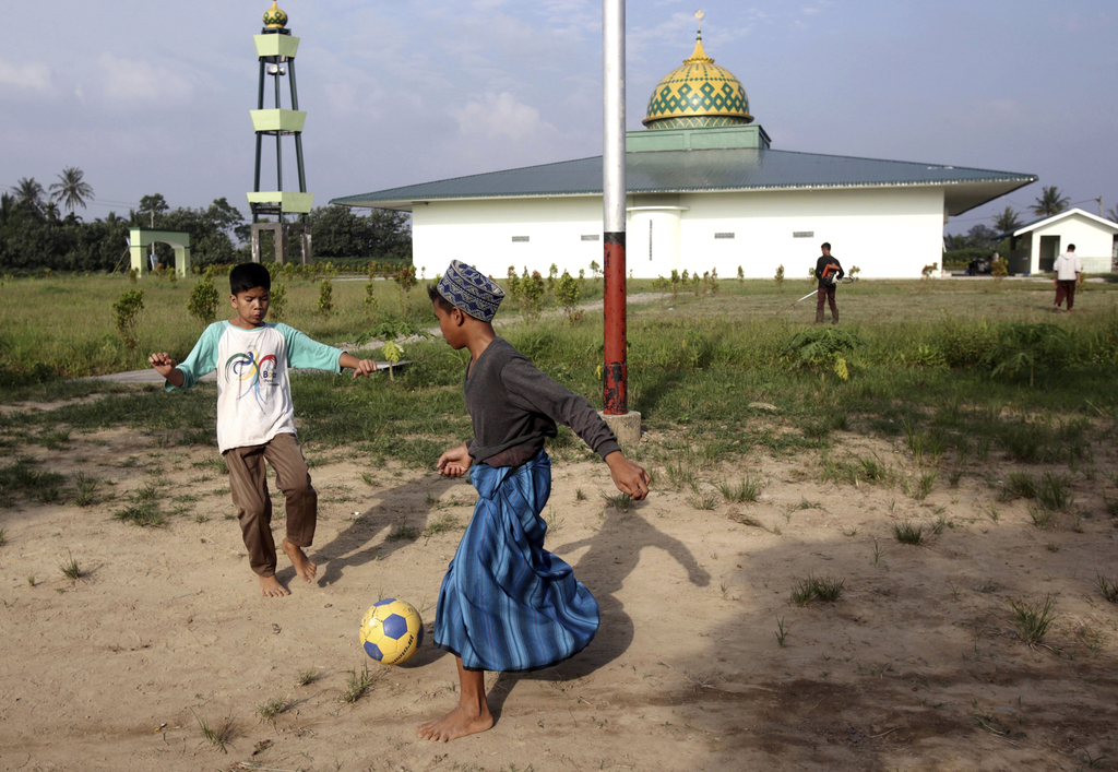 In this July 22, 2017, photo, students play soccer at Al Hidayah Islamic Boarding School in Sei Mencirim, North Sumatra, Indonesia. The school was fou...