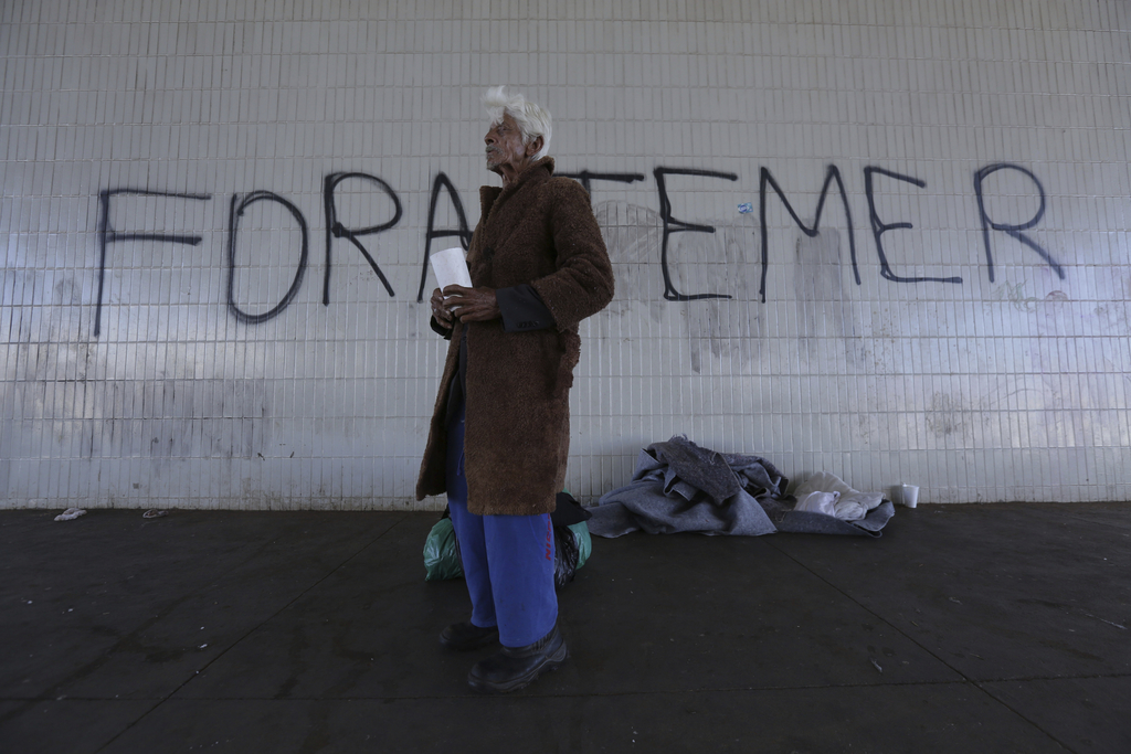 """A homeless person stands in front of graffiti that reads in Portuguese """"Temer Out,"""" in Brasilia, Brazil, Tuesday, Aug. 1, 2017. Brazilian President Mi..."""