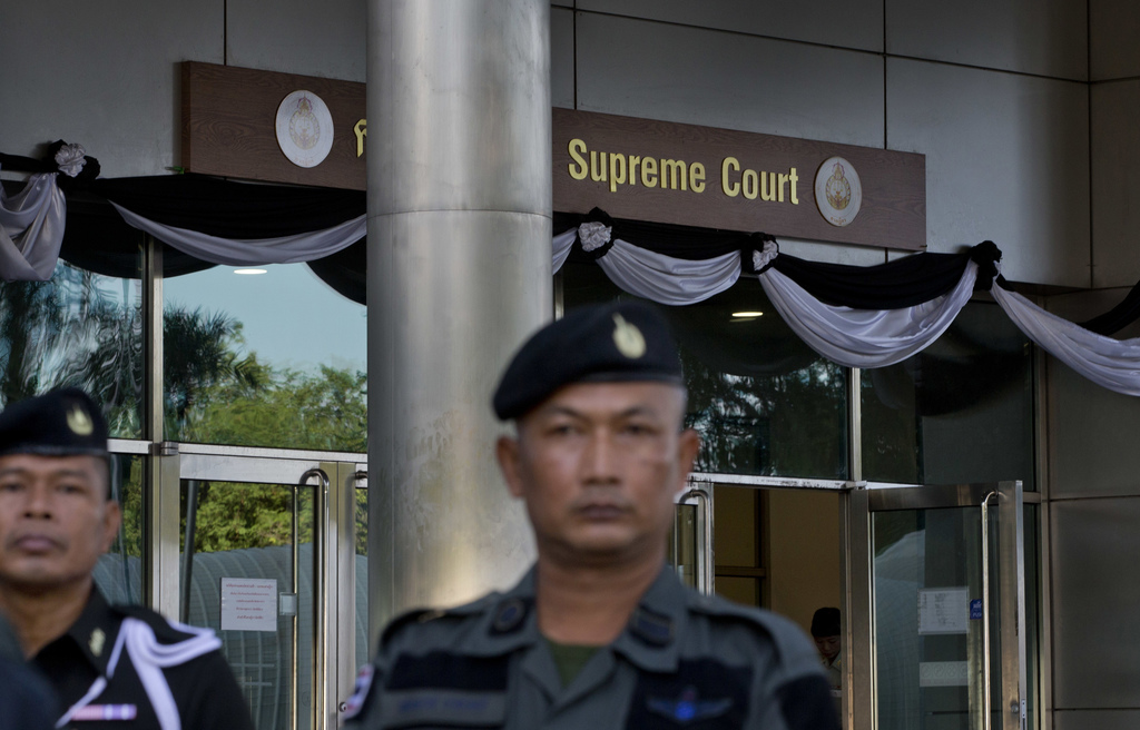 Police officers stand guard outside a courthouse ahead of the arrival of Thailand's former Prime Minister Somchai Wongsawat, Wednesday, Aug. 2, 2017, ...