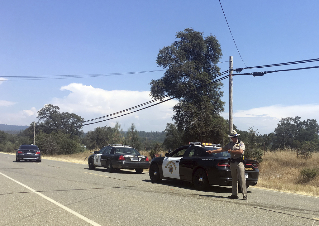Officers search for a suspect after a shooting in Dobbins, Calif., Tuesday, Aug. 1, 2017. Two California sheriff's deputies were shot and wounded Tues...