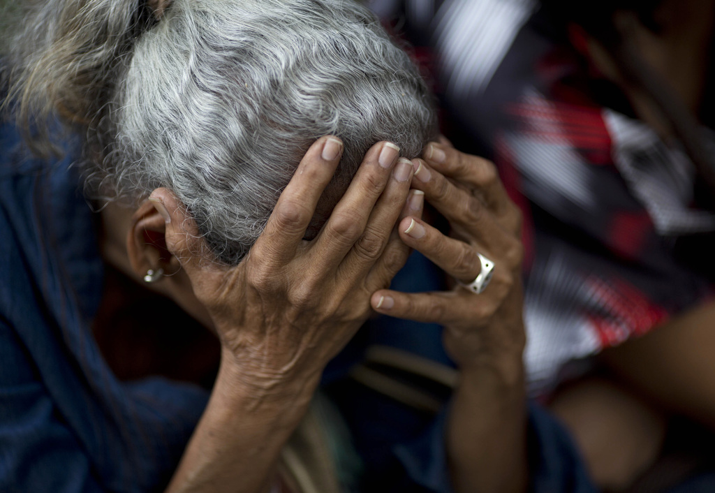 FILE - In this May 3, 2016 file photo, an elderly woman waits in line outside a supermarket to buy food in Caracas, Venezuela. Nine out of 10 people s...