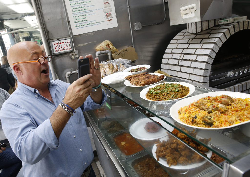 """In this Thursday, July 20, 2017 photo, the Travel Channel's """"Bizarre Foods"""" host Andrew Zimmern snaps a cell phone photo of chicken kebabs, far left, ..."""