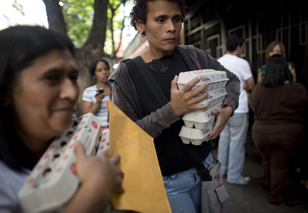 FILE - In this Jan. 27, 2016 file photo, people carry boxes of eggs after buying them at government regulated prices in Caracas, Venezuela, during an ...