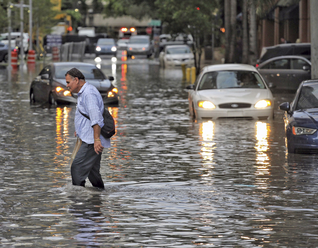 Pedestrians make their way through the flooded streets of the Brickell neighborhood of Miami, on Tuesday, Aug. 1, 2017. Tropical Depression Emily is n...