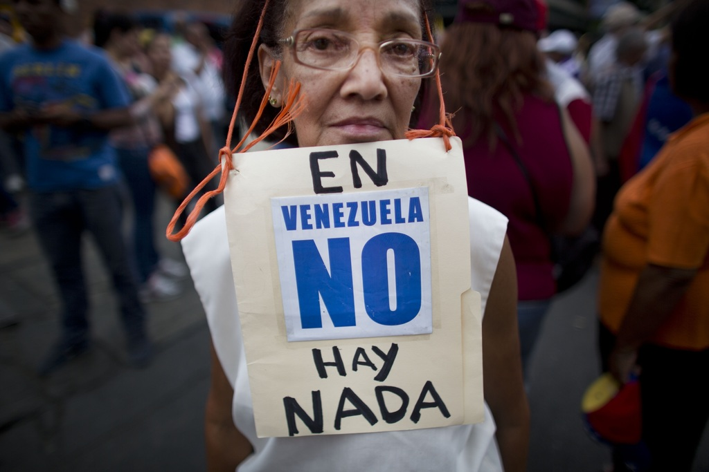 """FILE - In this Aug. 8, 2015 file photo, Beatriz Silva, 74, wears a sign that reads in Spanish: """"In Venezuela, there's nothing"""" as she joins a protest ..."""