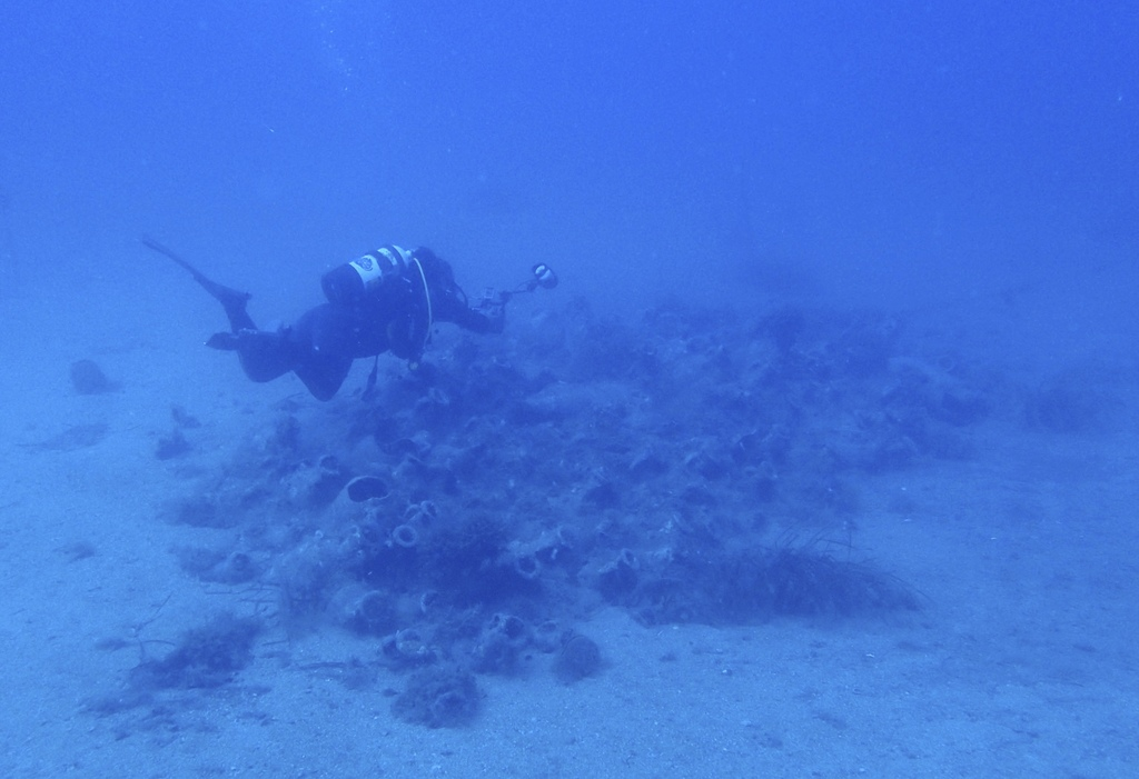 In this Wednesday, July 19, 2017 photo, a diver takes photographs of amphorae from a 4th century A.D. shipwreck off the coast of Albania. On the seabe...