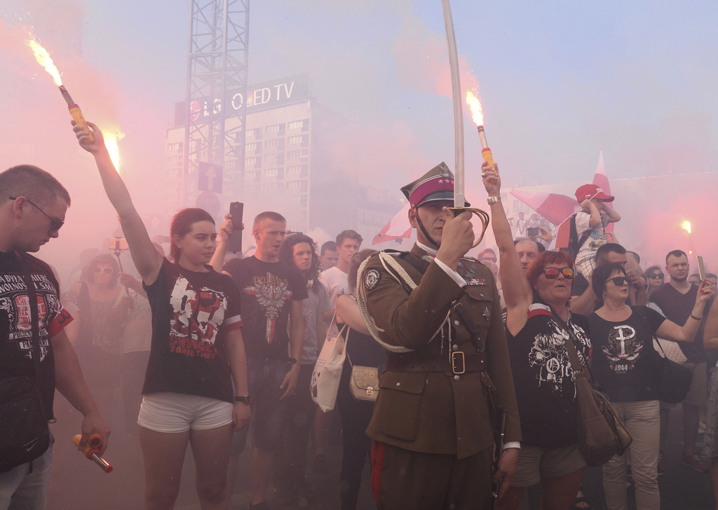 People stand on the city's main intersection holding burning flares to commemorate the 73rd anniversary of the 1944 Warsaw Uprising in Warsaw, Poland,...