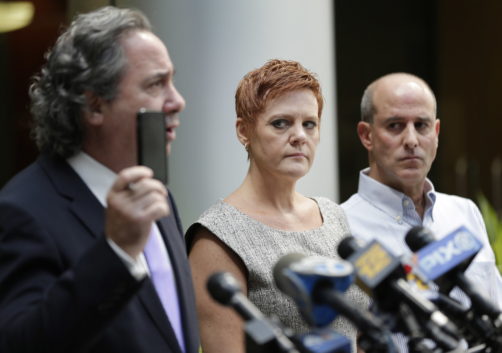 Dianne, center, and Seth Grossman, right, parents of Mallory Grossman, look as their attorney, Bruce Nagel, holds up a cell phone during a news confer...