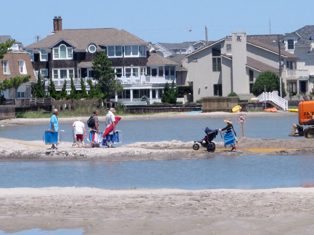 Beachgoers cross over one of numerous large pools of water that have formed on the beach in Margate N.J. due to heavy rains Monday July 31, 2017. The ...