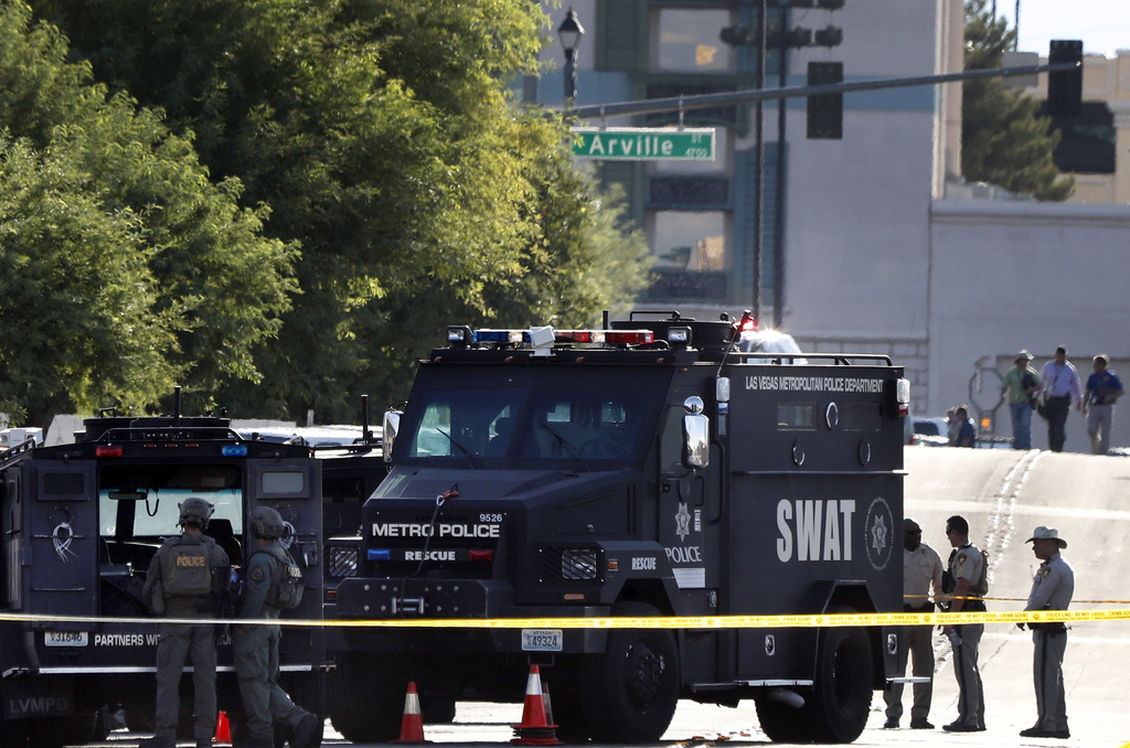 SWAT vehicles and officers stand on scene in Las Vegas after a police officer was shot Tuesday, Aug. 1, 2017. Police in Las Vegas say an officer is in...