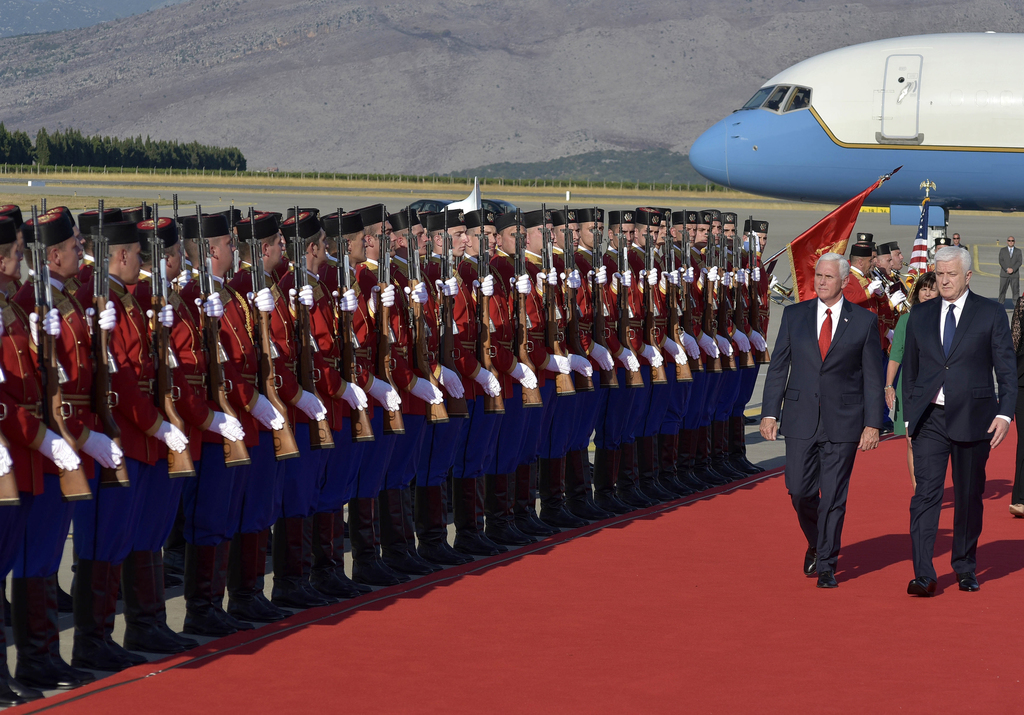 U.S. Vice President Mike Pence, second right, and Montenegro Prime Minister Dusko Markovic, right, attend a welcome ceremony at Golubovci airport, nea...