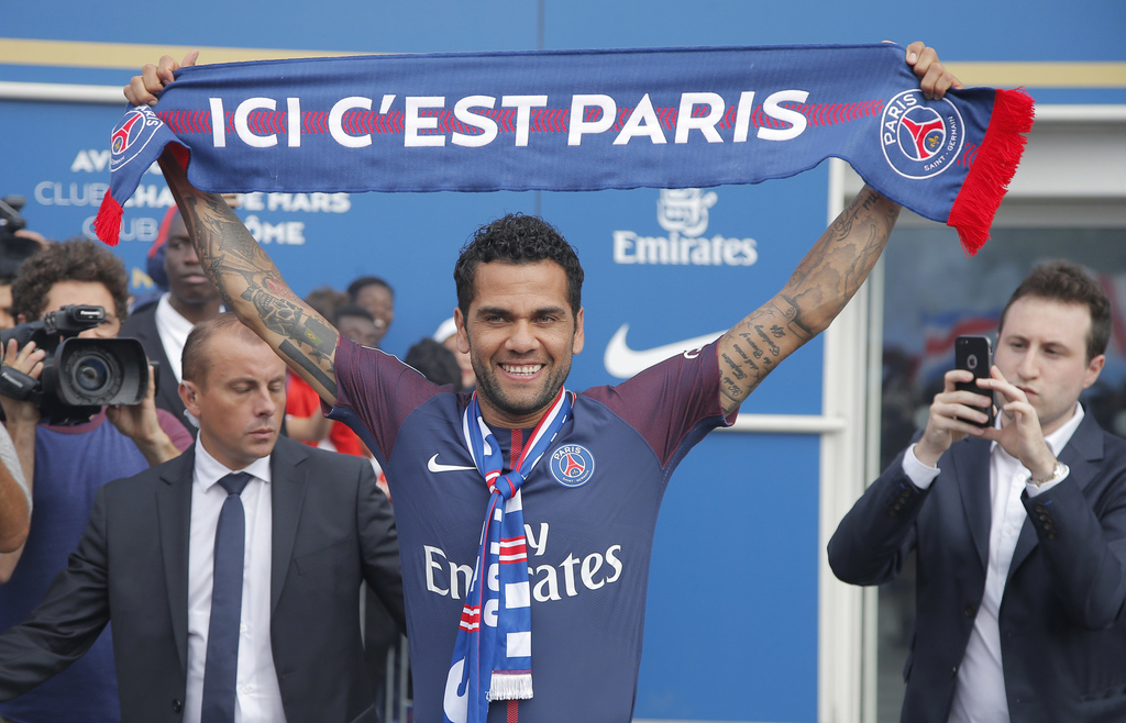 """FILE- In this July 12, 2017 file photo, Brazilian soccer player Dani Alves holds a scarf which reads """"this is Paris"""" as he acknowledges applauded of s..."""