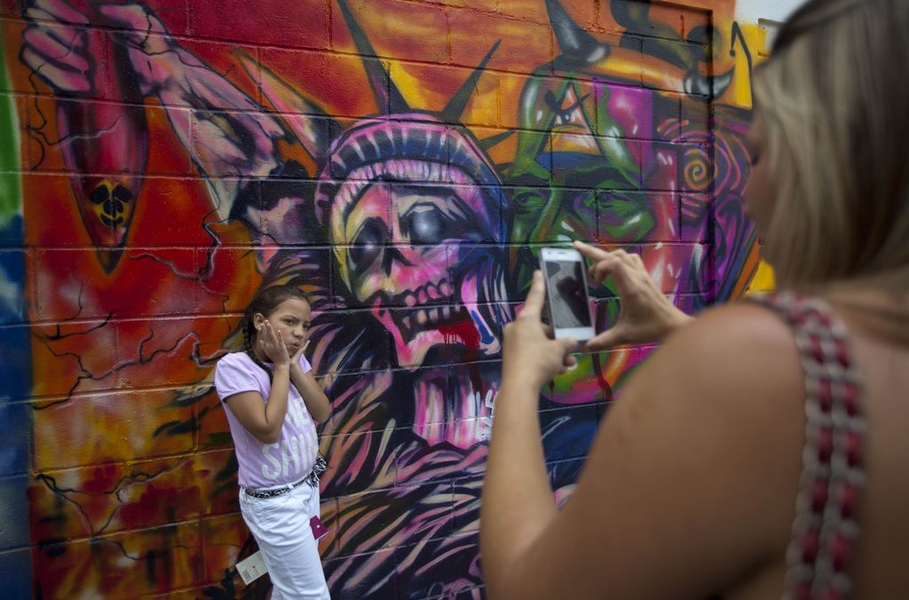 FILE - In this March 19, 2015 file photo, a girl poses for a picture in front of a mural depicting the statue of liberty as death, at Bolivar square i...