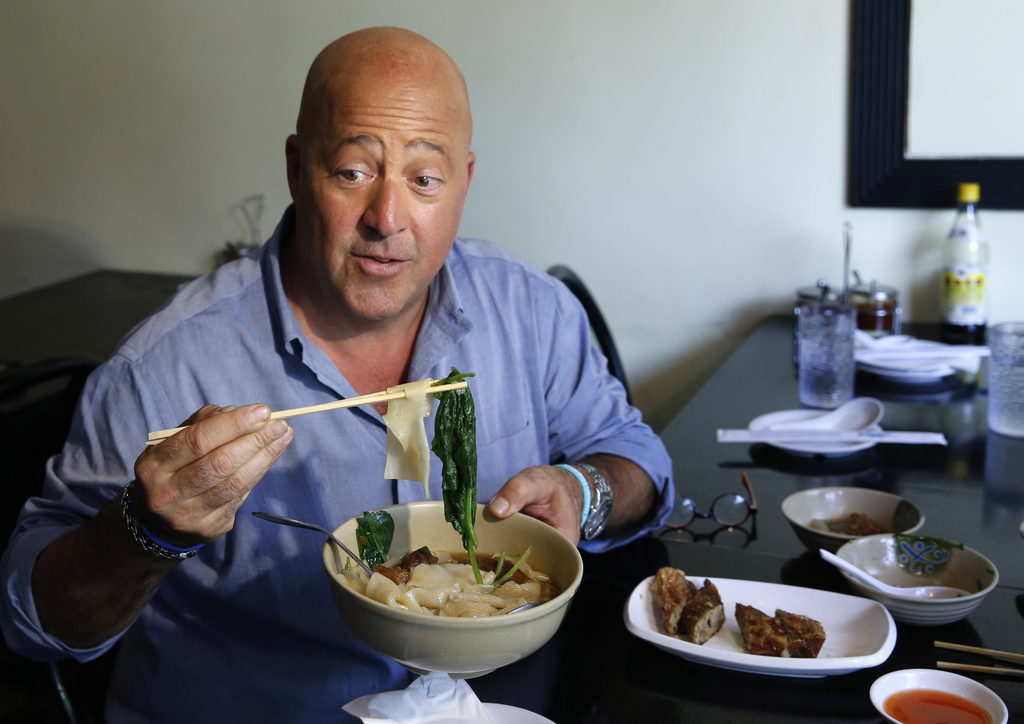 """In this Thursday, July 20, 2017 photo, Travel Channel's """"Bizzare Foods"""" host Andrew Zimmern, a four-time James Beard award-winning chef, samples Taiwa..."""