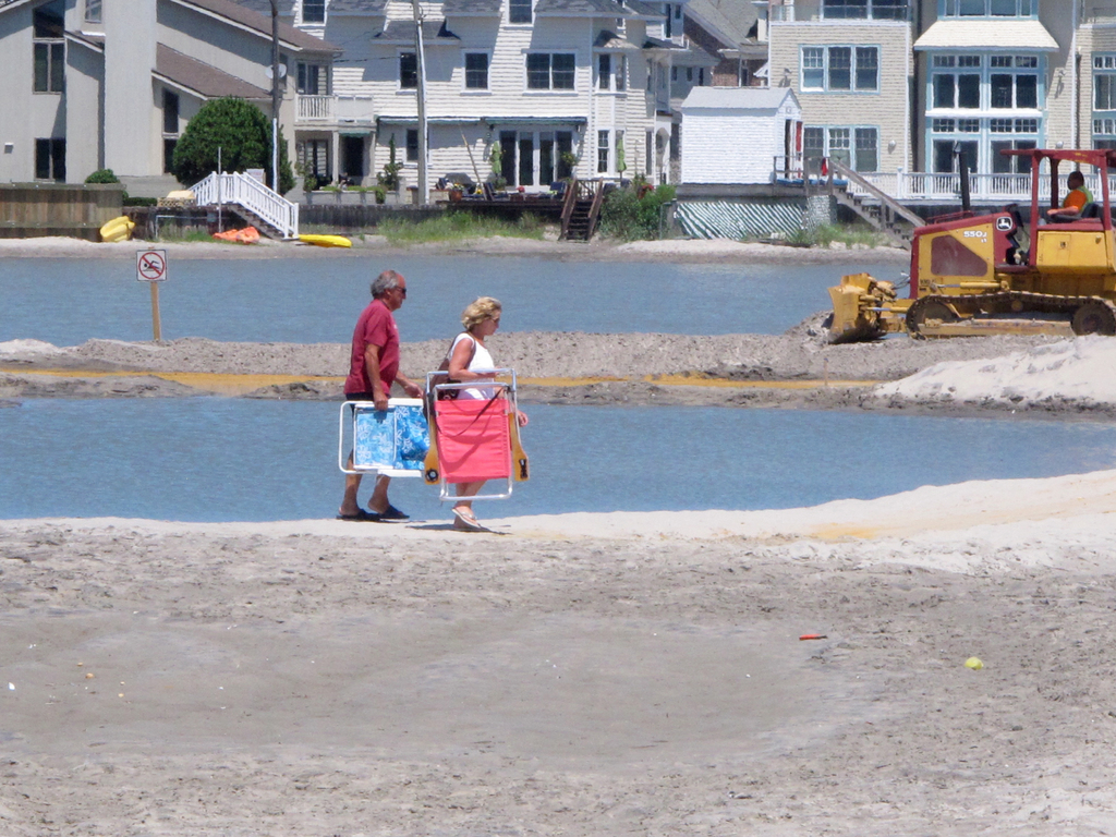 Beachgoers cross over one of numerous large pools of water that have formed on the beach in Margate N.J. due to heavy rains, Monday July 31, 2017. The...