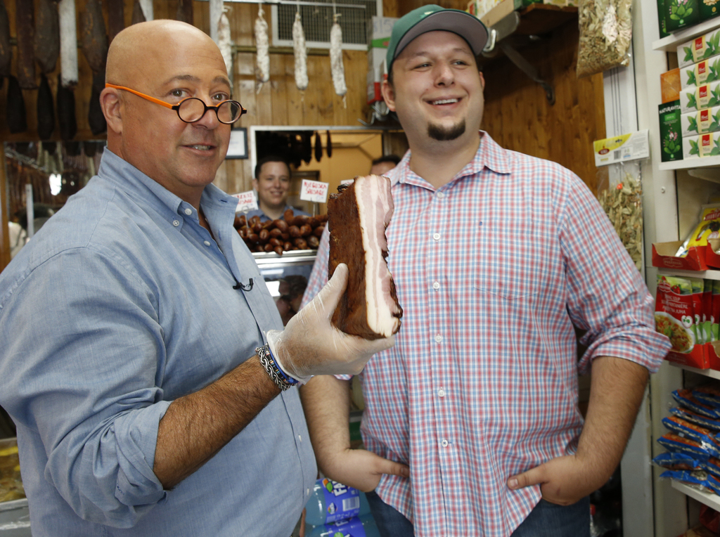 """In this photo taken Thursday, July 20, 2017, """"Bizarre Foods"""" host Andrew Zimmern, left, holds a slab of Carska bacon after savoring a small piece of i..."""
