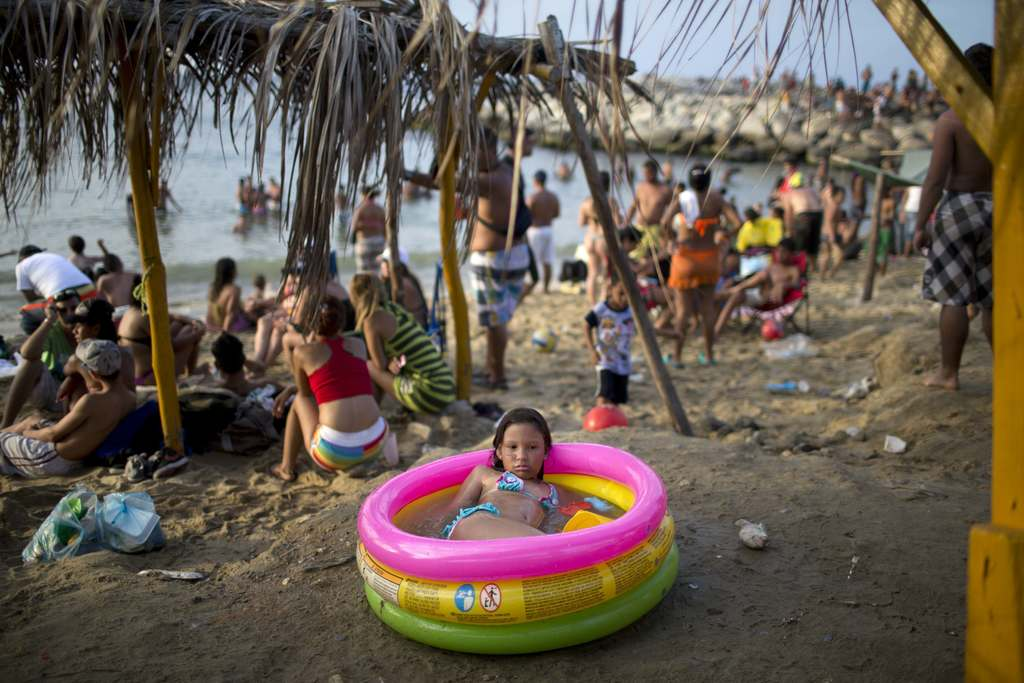 FILE - In this March 3, 2014 file photo, a girl cools off in an inflatable swimming pool on the beach in La Guaira, Venezuela. Some Venezuelans took t...