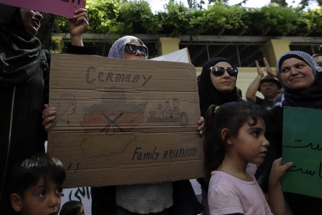 Nadja Mohamed from Syria, holds a placard during a protest outside the German Embassy in Athens, on Wednesday, Aug. 2, 2017. About 150 people, most of...
