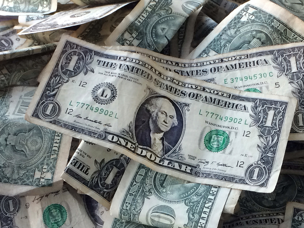 This Oct. 24, 2016, photo shows dollar bills in New York. Fraudsters are increasingly picking up the phone and trying to steal your money by pretendin...