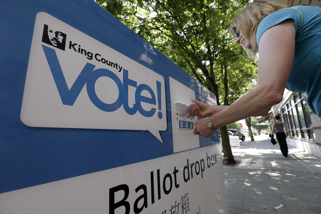 A woman drops a ballot in a voting box as voters cast ballots to start choosing a new mayor, Tuesday, Aug. 1, 2017, in Seattle. Voters were choosing f...