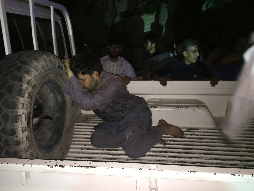 A wounded man rests on a vehicle after a suicide attack on a mosque in Heart, Afghanistan, Tuesday, Aug. 1, 2017. An Afghan hospital official says an ...