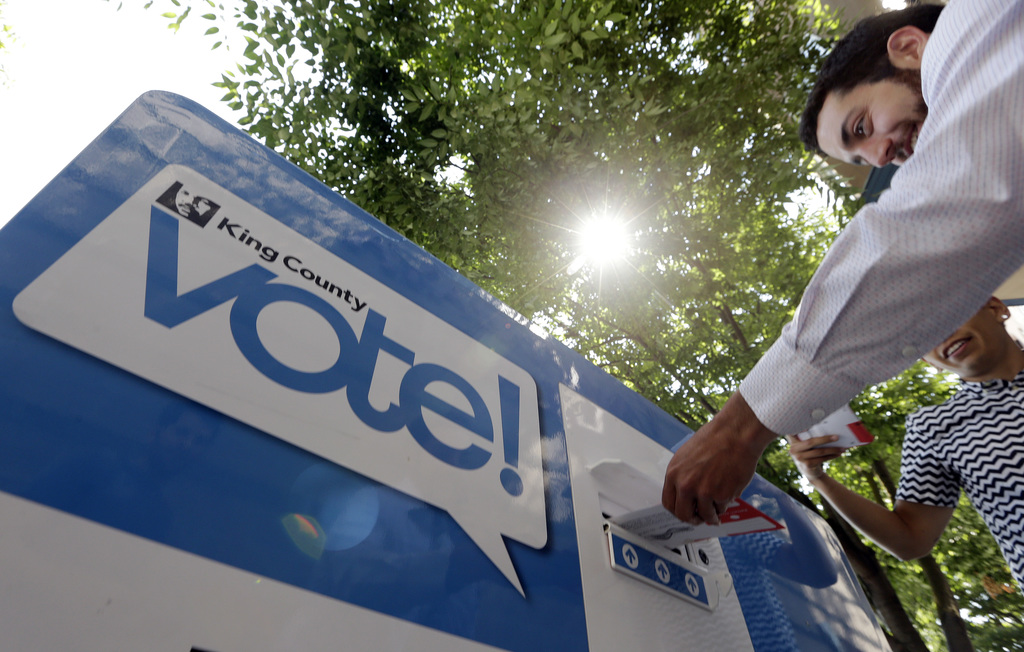 One man drops a ballot in a voting box as another waits as voters cast ballots to start choosing a new mayor, Tuesday, Aug. 1, 2017, in Seattle. Voter...