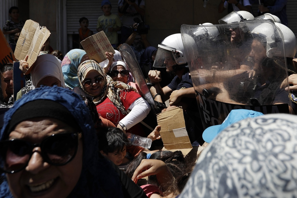 Stranded migrants and refugees scuffle with riot policemen outside the German Embassy during a protest in Athens, on Wednesday, Aug. 2, 2017. About 15...