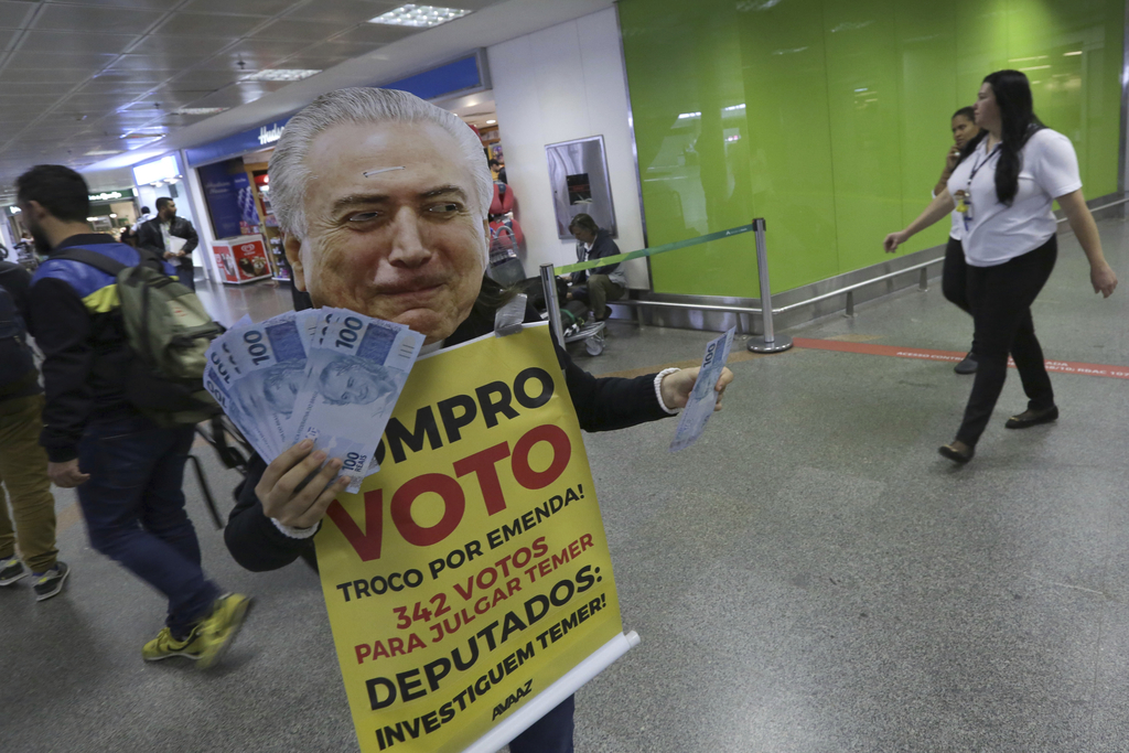 An activist protests, dressed with a mask of Brazil's President Michel Temer, as he holds fake 100 Brazilian Real notes and a sign that reads in Portu...