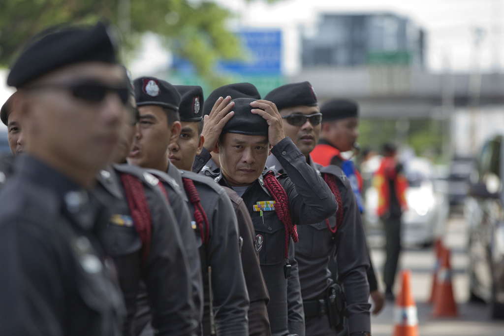 A police officer standing guard outside a courthouse adjusts his headwear ahead of the arrival of Thailand's former Prime Minister Somchai Wongsawat, ...