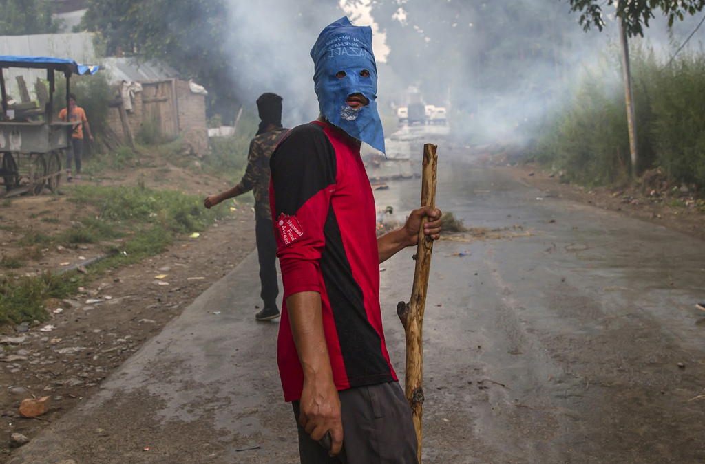 A masked villager holds a wooden stick and a stones during a protest following the funeral procession of Akeel Ahmed Bhat, a teenage boy in Haal villa...