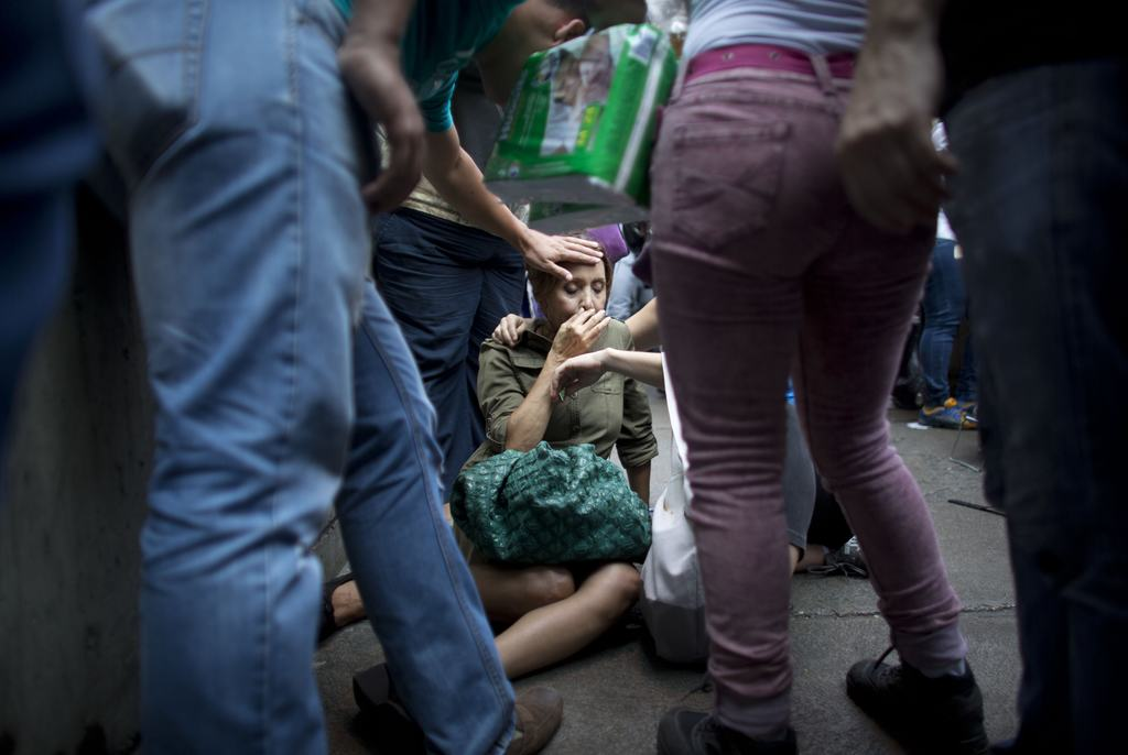 FILE - In this May 5, 2016 file photo, Irama Carrero is aided by fellow shoppers after fainting while waiting in a food line outside a grocery store, ...