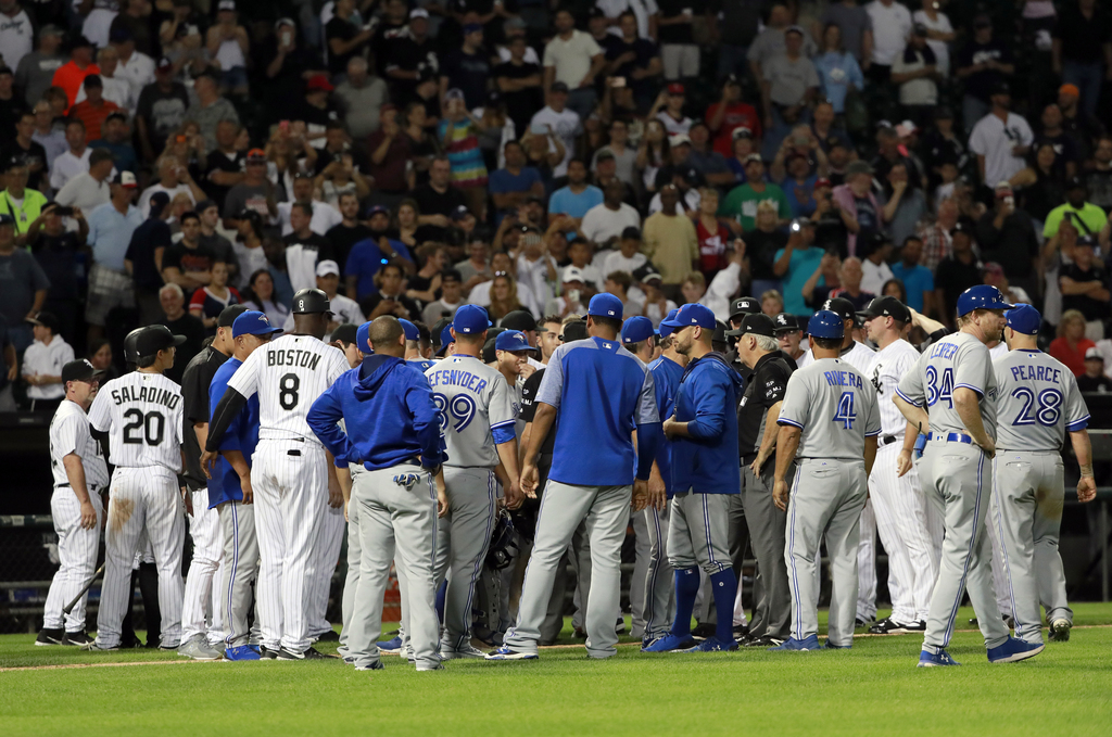 Payers, umpires and others gather during the seventh inning of a baseball game between the Toronto Blue Jays and the Chicago White Sox in Chicago, on ...