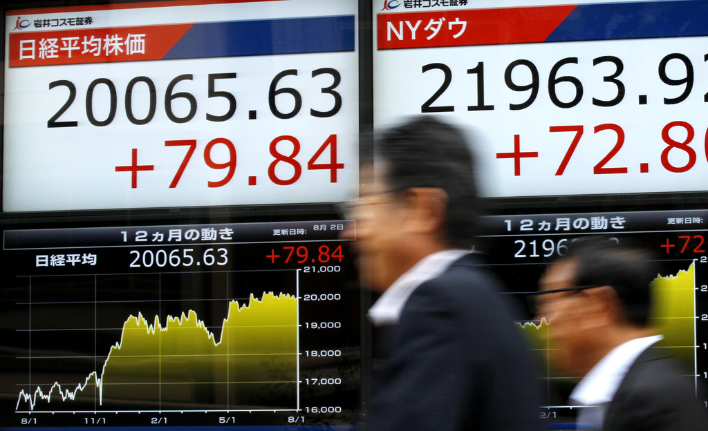 Men walk by an electronic stock board of a securities firm in Tokyo, Wednesday, Aug. 2, 2017. Asian stock markets were higher on Wednesday following D...