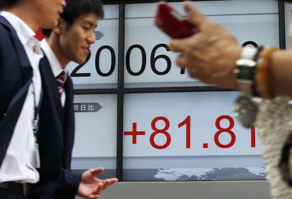 People pass by an electronic stock board of a securities firm in Tokyo, on Wednesday, Aug. 2, 2017. Asian stock markets were higher on Wednesday follo...