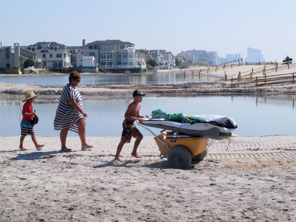 Beachgoers cross over one of numerous large pools of water that have formed on the beach in Margate N.J. due to heavy rains Tuesday, Aug. 1, 2017. The...