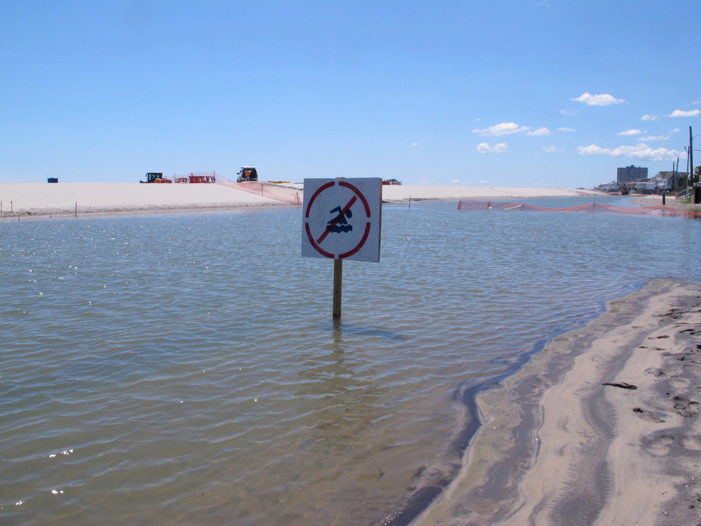 This July 31, 2017 photo shows a no swimming sign in one of numerous large pools of water that have formed on the beach in Margate N.J. due to heavy r...