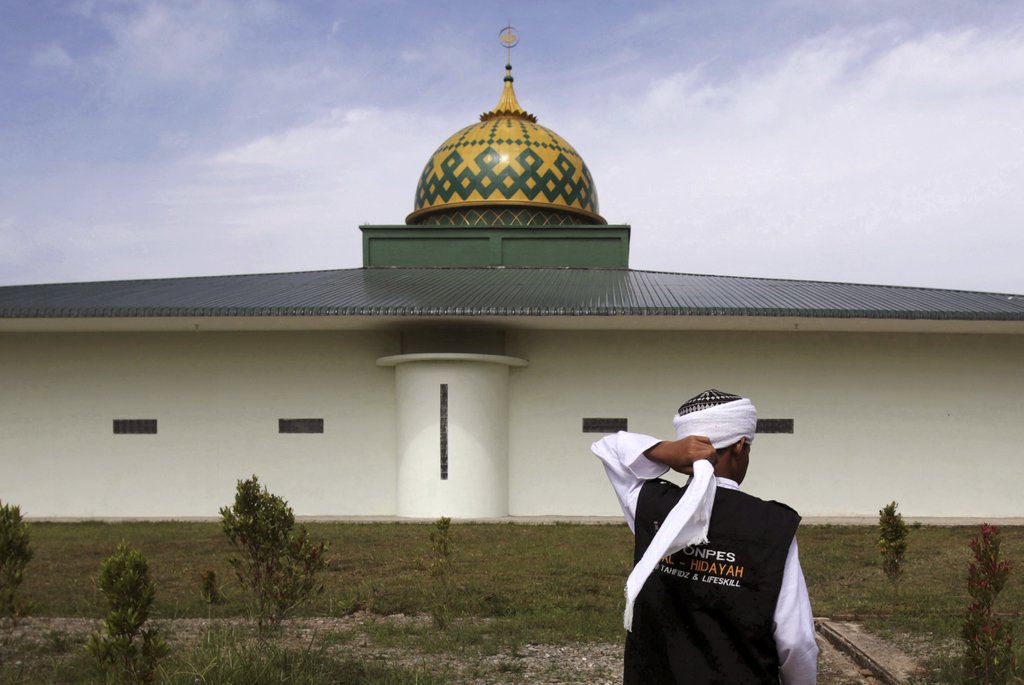 In this July 22, 2017, photo, a student adjusts his turban outside the mosque at Al Hidayah Islamic Boarding School in Sei Mencirim, North Sumatra, In...