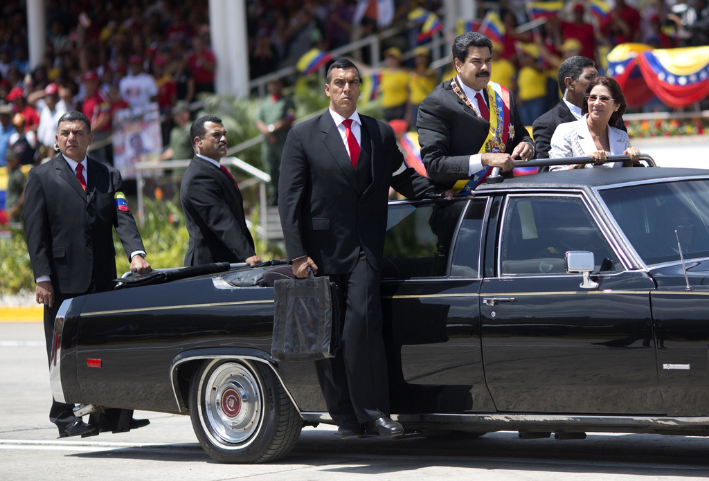 FILE - In this March 5, 2014 file photo, Venezuela's President Nicolas Maduro and first lady Cilia Flores are surrounded by security guards during a m...