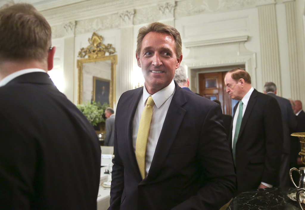FILE - In this July 19, 2017, file photo, Sen. Jeff Flake, R-Ariz., center, walks to his seat as he attends a luncheon with other GOP Senators and Pre...