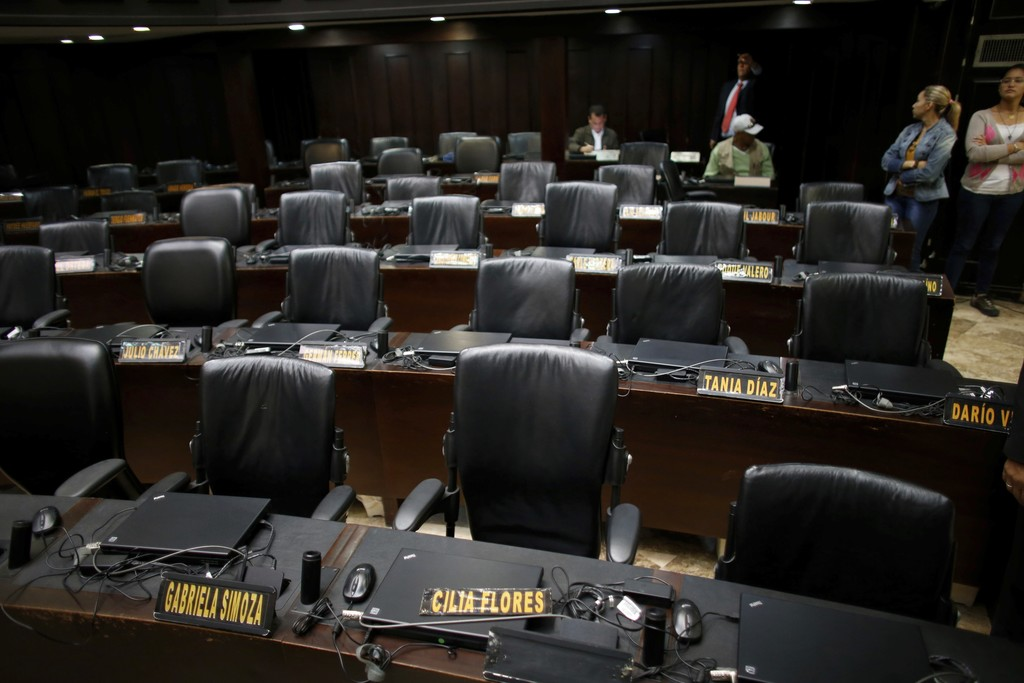 The seats of pro-government lawmakers sit empty during a session of Venezuela's National Assembly in Caracas, Wednesday, Aug. 2, 2017. The president o...