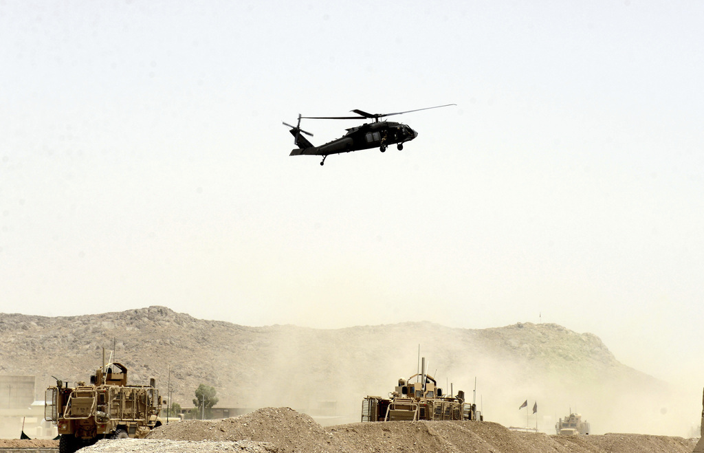 A US military helicopter flies over the site of a suicide bomb that struck a NATO convoy in Kandahar south of Kabul, Afghanistan, Wednesday, Aug. 2, 2...