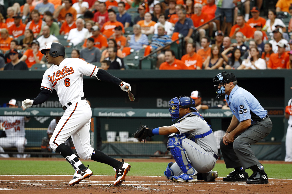 Baltimore Orioles' Jonathan Schoop, left, singles in front of Kansas City Royals catcher Salvador Perez and home plate umpire Angel Hernandez in the f...