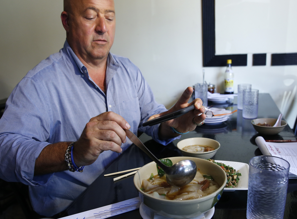 """In this Thursday, July 20, 2017 photo, Travel Channel's """"Bizzare Foods"""" host Andrew Zimmern, a four-time James Beard award-winning chef, takes a cell ..."""