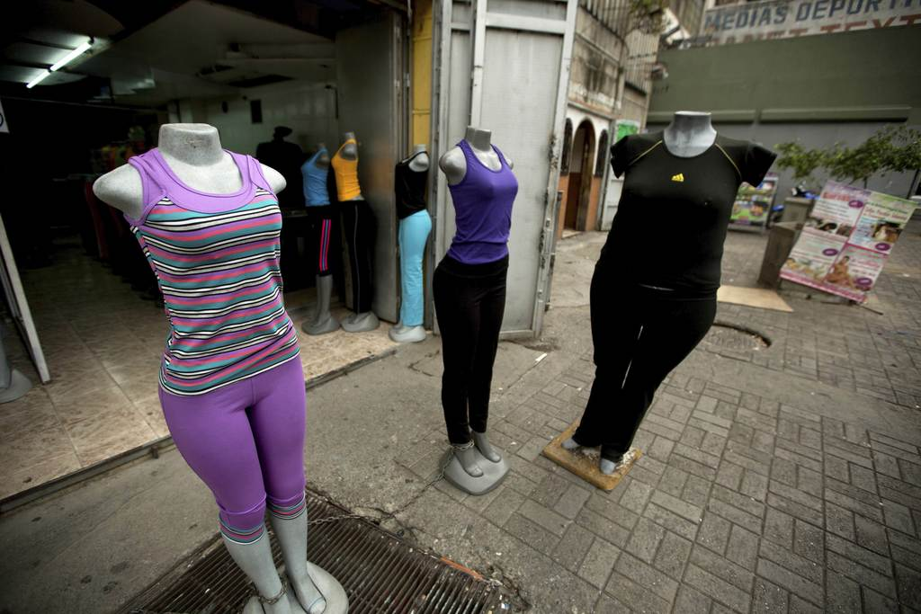 FILE - In this Aug. 26, 2014 file photo, a store advertises plus size clothing, right, in downtown Caracas, Venezuela. The Venezuelan government launc...
