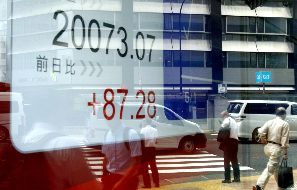 Pedestrians passing by are reflected on an electronic stock board showing Japan's Nikkei 225 index at a securities firm in Tokyo, on Wednesday, Aug. 2...