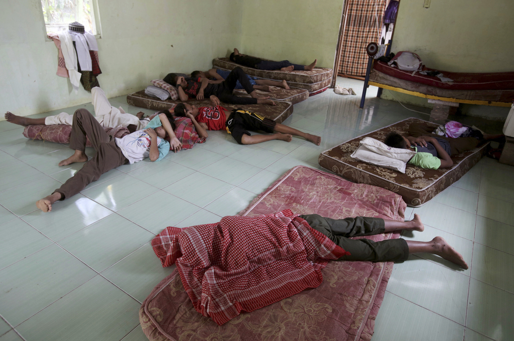 In this July 22, 2017, photo, students take a nap in their sleeping quarter at Al Hidayah Islamic Boarding School in Sei Mencirim, North Sumatra, Indo...