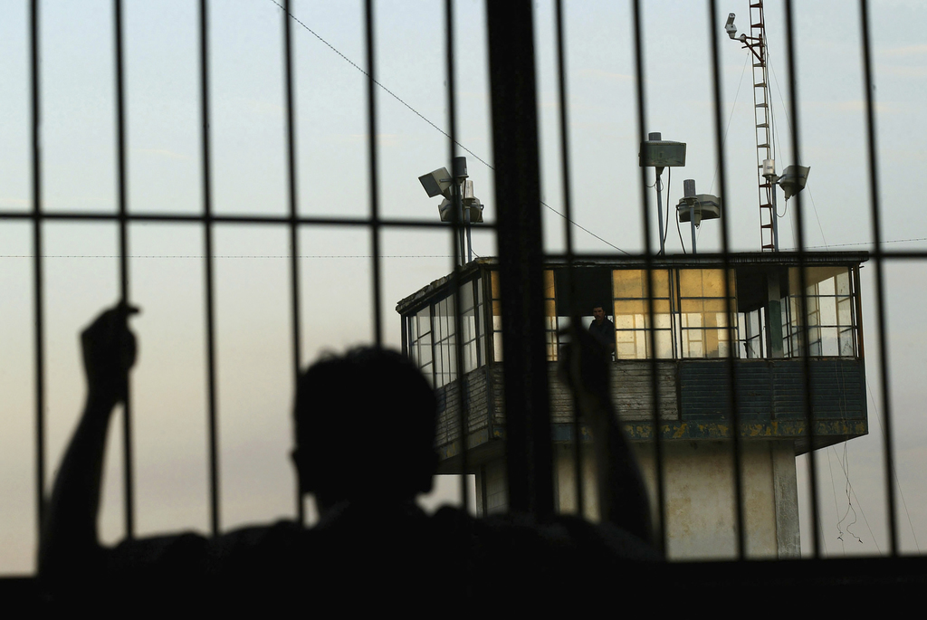 FILE - In this Jan. 19, 2005 file photo, an inmate looks out from behind bars as a guard watches from a security tower at the Nayarit State Prison, in...